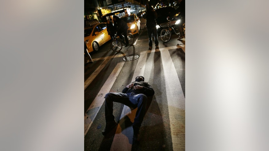 A protesters blocks traffic during a march in response to the grand jury's decision in the Eric Garner case in New York, Wednesday, Dec. 3, 2014. The grand jury cleared a white New York City police officer Wednesday in the videotaped chokehold death of Garner, an unarmed black man, who had been stopped on suspicion of selling loose, untaxed cigarettes, a lawyer for the victim's family said. (AP Photo/Seth Wenig)