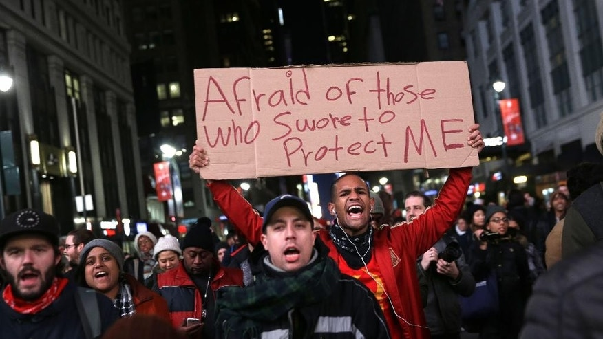 Protesters march through the streets in response to the grand jury's decision in the Eric Garner case in Times Square in New York, Wednesday, Dec. 3, 2014. The grand jury cleared a white New York City police officer Wednesday in the videotaped chokehold death of Garner, an unarmed black man, who had been stopped on suspicion of selling loose, untaxed cigarettes, a lawyer for the victim's family said. (AP Photo/Seth Wenig)