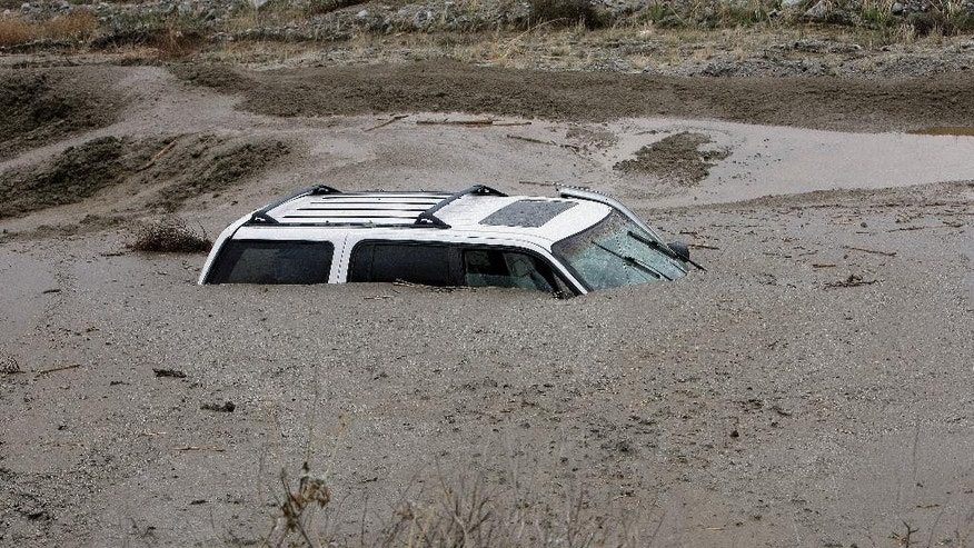 A vehicle sits in mud up to its windows on Soboba Road near Gilman Springs Road in San Jacinto, Calif. on Thursday, Dec. 4, 2014. Heavy rains triggered flash floods and stranded more than three dozen people in their cars in Southern California. (AP Photo/The Press-Enterprise, Frank Bellino)