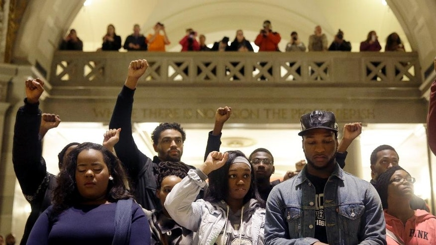 Protesters pause for a moment of silence in the rotunda of the Missouri Capitol after completing a 7-day march Friday, Dec. 5, 2014, in Jefferson City, Mo. Scores of people protesting the police shooting of Michael Brown arrived Friday at the Missouri Capitol, completing a 130-mile march from the shooting site in the St. Louis suburb of Ferguson. (AP Photo/Jeff Roberson)