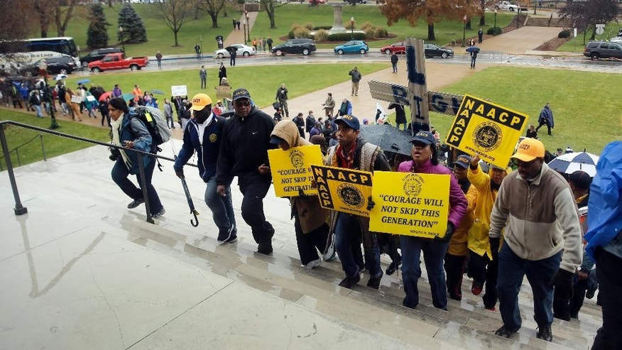 Marchers walk up the steps of the Missouri Capitol as they complete a 7-day march Friday, Dec. 5, 2014, in Jefferson City, Mo. Scores of people protesting the police shooting of Michael Brown finished the 130-mile march from the shooting site in the St. Louis suburb of Ferguson. (AP Photo/Jeff Roberson)