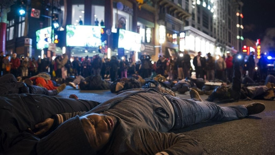 "Protestors stage a four and-a-half minute ""die-in""in downtown  Washington, Friday, Dec. 5, 2014, during a demonstration against the deaths of two unarmed black men at the hands of white police officers in New York City and Ferguson, Mo.  (AP Photo/Cliff Owen)"