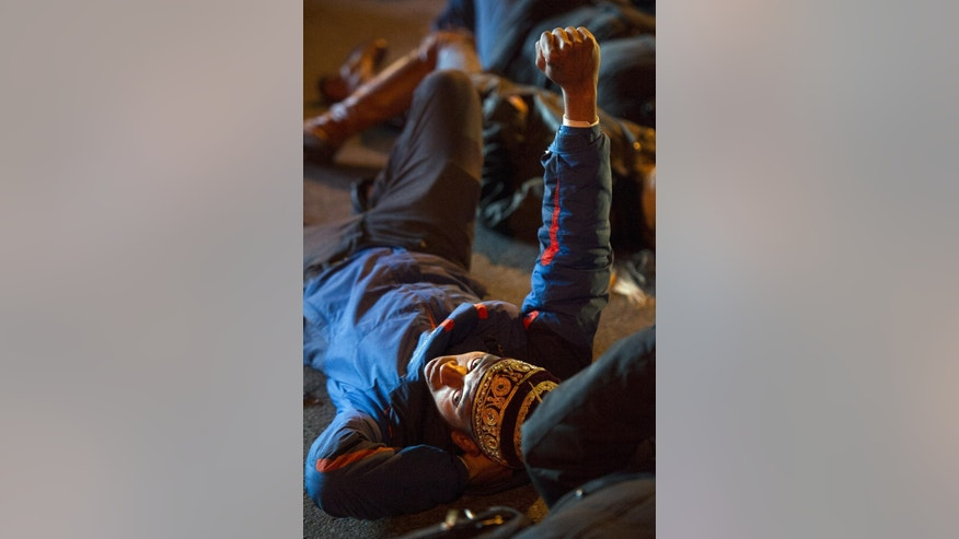 "Deon Johnson, 19, of Washington, DC, raises his fist as he and others take part in a four and-a-half minute ""die-in"" while blocking an intersection in downtown,Washington, Friday, Dec. 5, 2014, during a demonstration against the deaths of two unarmed black men at the hands of white police officers in New York City and Ferguson, Mo.  (AP Photo/Cliff Owen)"