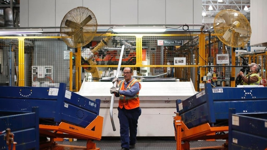 In this Nov. 11, 2014 photo, Agil Alhaddi stacks roof rails for the 2015 Ford F-150 at the Dearborn Truck Plant in Dearborn, Mich. The Commerce Department releases factory orders for October on Friday, Dec. 5, 2014. (AP Photo/Paul Sancya)