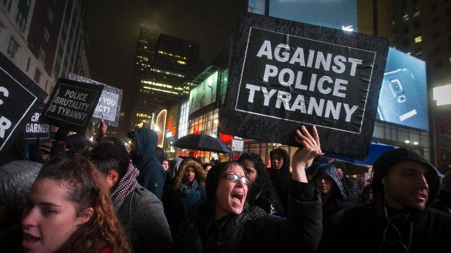 Protesters rallying against a grand jury's decision not to indict the police officer involved in the death of Eric Garner block traffic on 34th Street, Friday, Dec. 5, 2014, in New York. (AP Photo/John Minchillo)