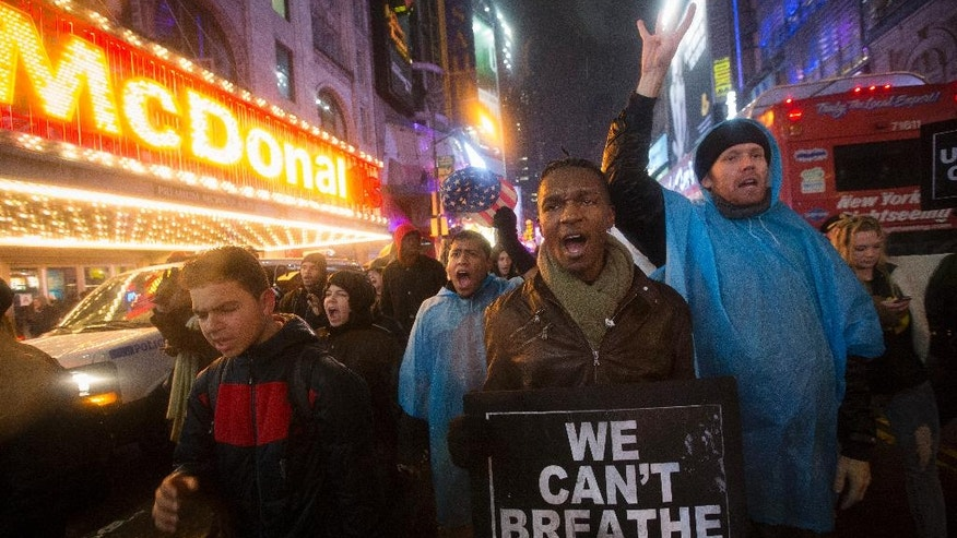 Protesters march against a grand jury's decision not to indict the police officer involved in the death of Eric Garner, Friday, Dec. 5, 2014, in New York. (AP Photo/John Minchillo)