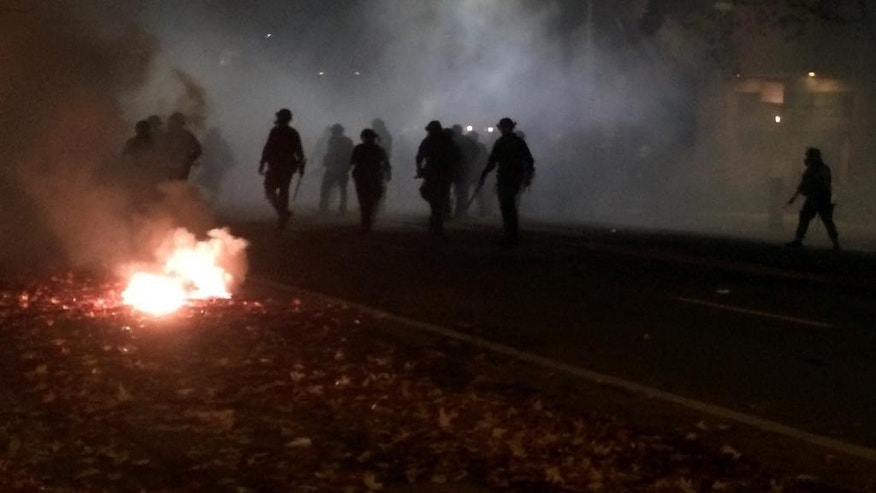 In this photo provided by Tay Nitta, police in riot gear patrol a street in Berkeley, Calif. amid smoke and tear gas after a protest over police killings turned violent, early Sunday, Dec. 7, 2014. Two officers were injured in the protests, with protesters smashing windows and throwing rocks and bricks at police, who responded by firing tear gas, authorities said. (AP Photo/Tay Nitta)