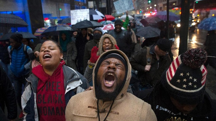 "Protestors march along 42nd Street following  a ""die-in"" at Grand Central Station against a grand jury's decision not to indict the police officer involved in the death of Eric Garner, Saturday, Dec. 6, 2014, in New York. (AP Photo/John Minchillo)"
