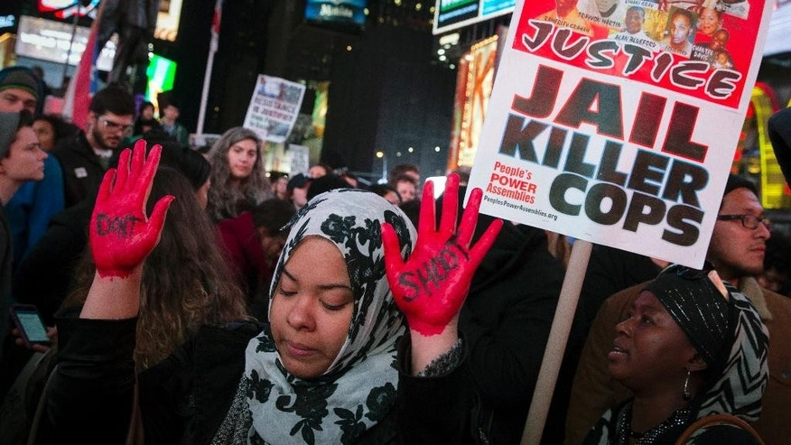 FILE- In this Nov. 25, 2014 file photo, demonstrator Maryam Said raises her painted hands during a protest against a grand jury's decision on Monday not to indict Ferguson police officer Darren Wilson in the shooting of Michael Brown in New York. No firm statistics can say whether a spate of officer-involved deaths is a growing trend or simply a series of coincidences generating a deafening buzz in news reports and social media. (AP Photo/John Minchillo, File)
