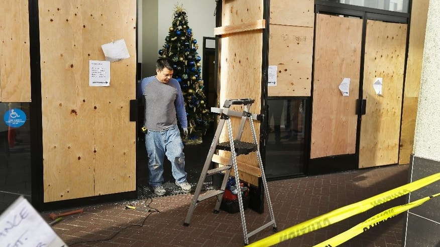 A worker pauses as he cleans up damage to Chase bank Monday, Dec. 8, 2014, the result of a violent protest Sunday night in Berkeley, Calif. The second straight night of protests in Berkeley over police killings in Missouri and New York led to at least five arrests and left two officers with minor injuries. (AP Photo/Ben Margot)