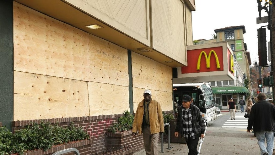 Pedestrians pass vandalism damage to the storefront of McDonald's Monday, Dec. 8, 2014, the result of a violent protest Sunday night, in Berkeley, Calif. A second straight night of protests in Berkeley over police killings in Missouri and New York led to at least five arrests and left two officers with minor injuries. (AP Photo/Ben Margot)