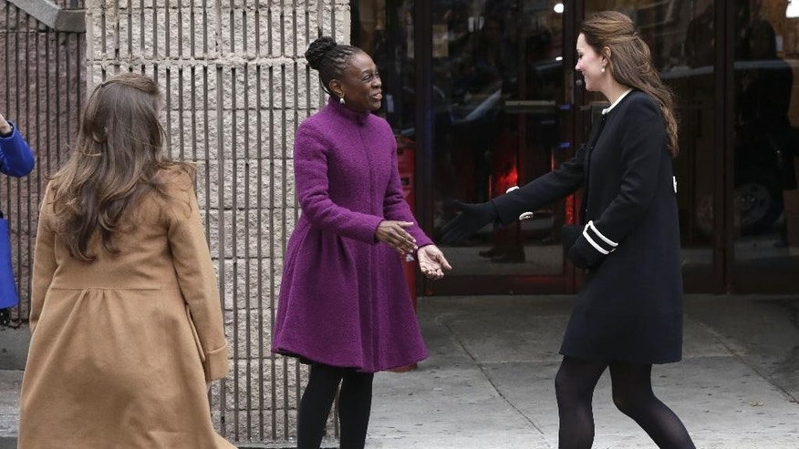 Kate, the Duchess of Cambridge, right, is greeted by New York City first lady Chirlane McCray at the Northside Center for Child Development, Monday, Dec. 8, 2014 in New York. Kate was greeted with cheers from a crowd of several dozen spectators standing behind police barricades across the street before entering to meet with volunteers and students participating in a craft making exercise. (AP Photo/Richard Drew)