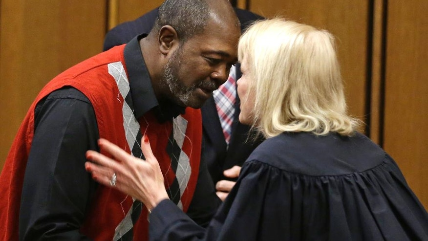 Ronnie Bridgeman, now known as Kwame Ajamu, gets a hug from Judge Pamela A. Barker after charges were dismissed against Ajamu Tuesday, Dec. 9, 2014, in Cleveland.  Ajamu, the last of three men convicted and sentenced to death in the 1975 slaying of an Ohio businessman had his charges dismissed.  Ajamu was 17 when he was convicted in the shooting death of Harry Franks outside a Cleveland corner store. He was released from prison in January 2003 after 27 years behind bars. His brother, Wylie Bridgeman, and their best friend from the neighborhood, Ricky Jackson, were released from prison late last month after serving nearly 40 years.  (AP Photo/Tony Dejak)