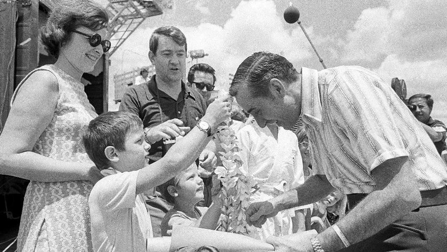 FILE - In this March 31, 1973, file photo, a boy places a Lei over the head of Ernest Brace before the returned POW departs for the U.S. from Tokyo, Japan.  Brace, who was captured flying supplies to a base in Laos for the CIA during the Vietnam War and spent more than a year in the Hanoi Hilton tapping code through a wall to Sen. John McCain, has died Friday, Dec. 5, 2014, in Klamath Falls, Ore., his family said. He was 83. (AP Photo/File)