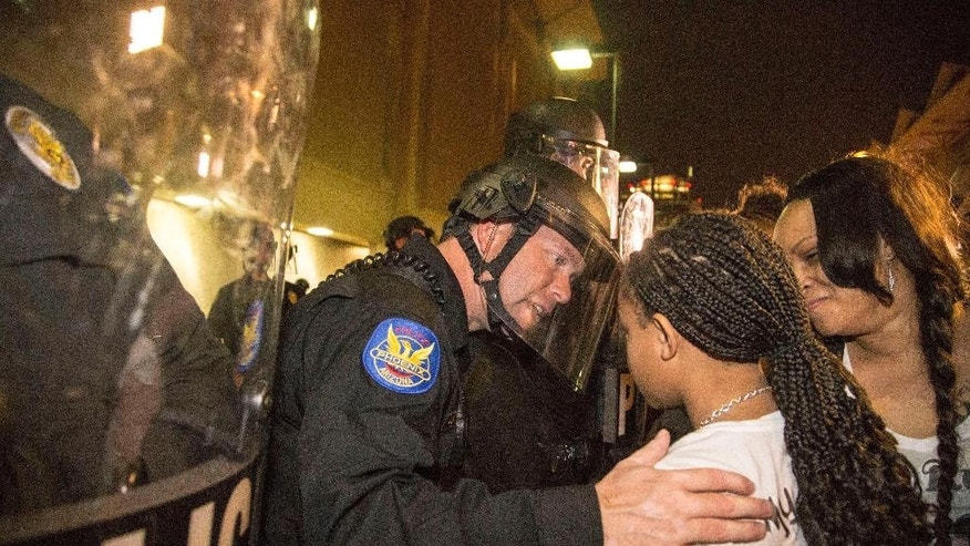 "In this Monday, Dec. 8, 2014 photo, a Phoenix police officer in riot gear talks with Aiyana Rains, 9, the daughter of Rumain Brisbon, as she participates with hundreds of protesters headed towards police headquarters to demand transparency in the case that left her father dead following a confrontation with a police officer on Dec. 2. Grasping her hand, the officer said, ""I'm sorry."" (AP Photo/The Arizona Republic, Nick Oza)"