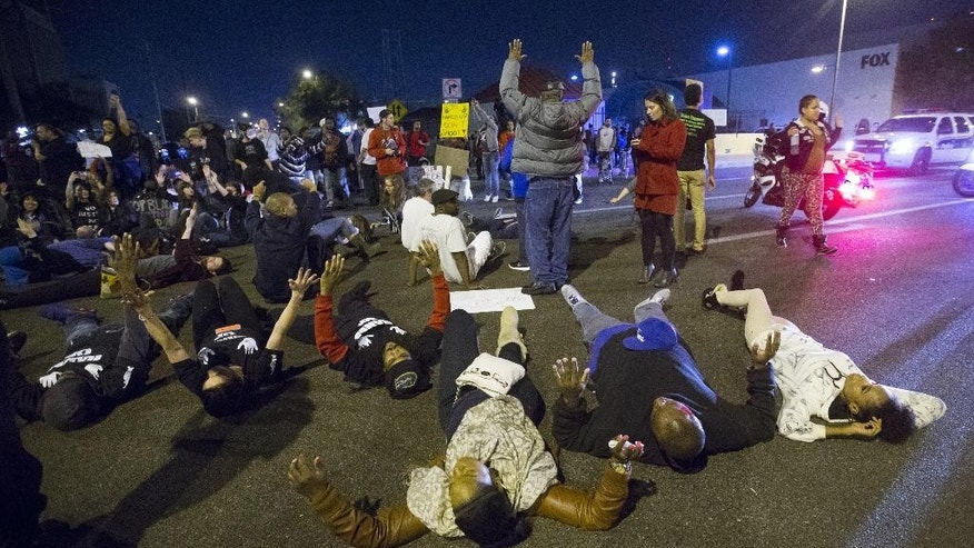 In this photo taken on Thursday, Dec. 4, 2014, people protest during a rally near Phoenix Police headquarters to protest the police killing of Rumain Brisbon, an unarmed black man. The mother and girlfriend of Brisbon, an unarmed drug suspect fatally shot by a Phoenix police officer who mistook a pill bottle for a gun, do not want the incident to become about race. The deadly shooting Tuesday, Dec. 2, of  Brisbon, 34, demonstrates the challenges law enforcement agencies face at a time of unrest over police tactics. Phoenix police say the officer, who is white, feared the suspect was armed during their struggle, but some critics say the officer went too far. Despite the department's efforts to be transparent with information, protesters marched Thursday night. (AP Photo/The Arizona Republic, Cheryl Evans )  MARICOPA COUNTY OUT; MAGS OUT; NO SALES