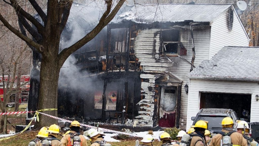 Montgomery County, Md., firefighters stand outside a house where a small private jet crashed in Gaithersburg, Md., Monday, Dec. 8, 2014. A woman and her two young sons inside the home and three people on the aircraft were killed, authorities said. (AP Photo/Jose Luis Magana)
