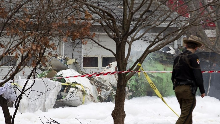 The wreckage of a small private jet smolders in a driveway after crashing into a neighboring house in Gaithersburg, Md., Monday, Dec. 8, 2014. A woman and her two young sons inside the home and three people aboard the aircraft were killed, authorities said. (AP Photo/Jose Luis Magana)