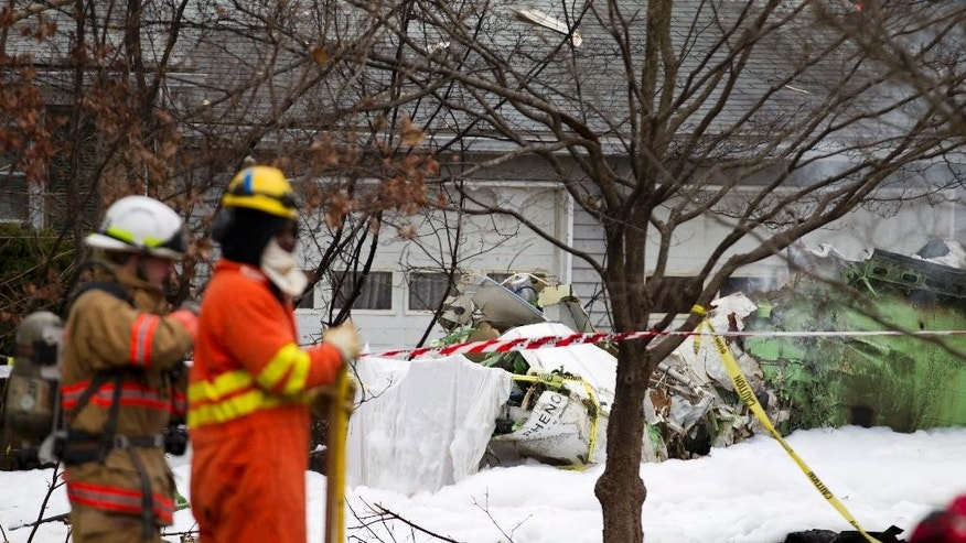 The wreckage of a small private jet sits in a driveway after crashing into a neighboring house in Gaithersburg, Md., Monday, Dec. 8, 2014. A woman and her two young sons inside the home and three people aboard the aircraft were killed, authorities said. (AP Photo/Jose Luis Magana)