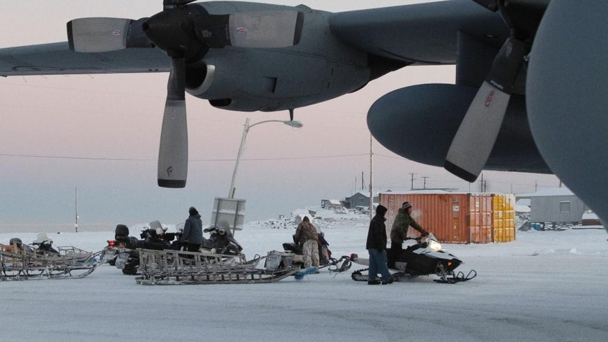 This photo taken Dec. 6, 2014, shows Christmas toys and other supplies being loaded from a C130 military transport plane onto sleds being pulled by snowmobiles in Shishmaref, Alaska. The Alaska National Guard provided transport for the good Samaritan program Operation Santa, which took gifts and schools supplies to about 300 children in the Inupiat Eskimo community. (AP Photo/Mark Thiessen)