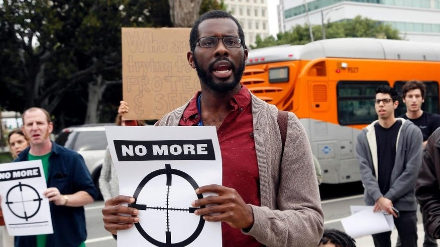 In this Dec. 5, 2014 photo, Yvorn Aswad protests outside Los Angeles police headquarters. Across the country, protesters angered at the killing of unarmed black men by white police officers have turned out in recent days in cities and towns. Aswad, a brother and his girlfriend, and a cousin decided to march then the protest in the center of Los Angeles. (AP Photo/Nick Ut)