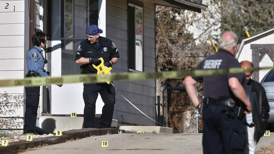 Law enforcement officers work among evidence markers placed in the driveway of a house where police are investigating the slayings of multiple people found inside the home, in the Denver suburb of Westminster, Colo., Wednesday, Dec. 10, 2014. According to Adams County Sheriff's Office, who have yet to release the number of victims, the bodies were found Wednesday morning after a distraught woman called 911 to report a disturbance in the home before hanging up. (AP Photo/Brennan Linsley)