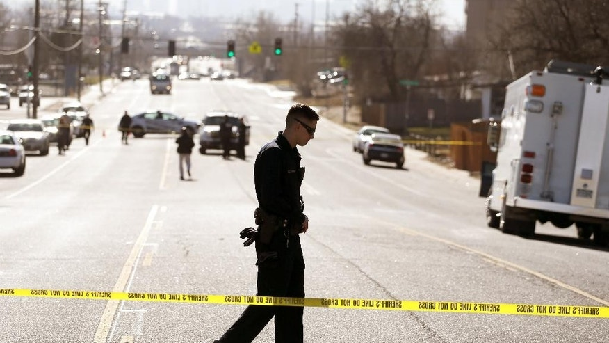 A law enforcement officer guards the perimeter of a crime scene where police are investigating the slayings of multiple people found inside a home, in the Denver suburb of Westminster, Colo., Wednesday, Dec. 10, 2014. According to the Adams County Sheriff's Office, the bodies were found earlier in the day after a distraught woman called 911 to report a disturbance in the home before hanging up. (AP Photo/Brennan Linsley)