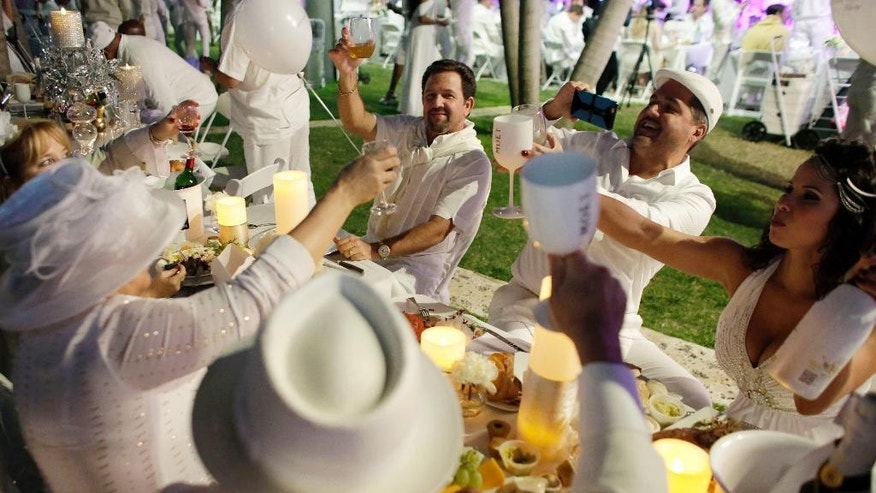 "Diners say a toast during  the ""Diner en Blanc"" event at SoundScape Park, Tuesday, Dec. 9, 2014, in Miami Beach, Fla. About a thousand people gathered at the pop-up picnic event that started in Paris in 1988 and has spread worldwide. Invitations are spread by word of mouth and the location of the dinner is kept secret until the last minute. (AP Photo/Lynne Sladky)"