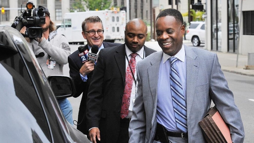 FILE - In this Oct. 1, 2014 file photo Detroit Emergency Financial Manager Kevyn Orr, right, leaves U.S. District Court in Detroit. Orr, in a letter to Monday, Dec. 8 to Gov. Rick Snyder, says the city no longer will be in a financial emergency when it officially exits bankruptcy. That means Orr's job will be done once the bankruptcy court approves the exit. (AP Photo/Detroit News, Daniel Mears)  DETROIT FREE PRESS OUT; HUFFINGTON POST OUT; MANDATORY CREDIT