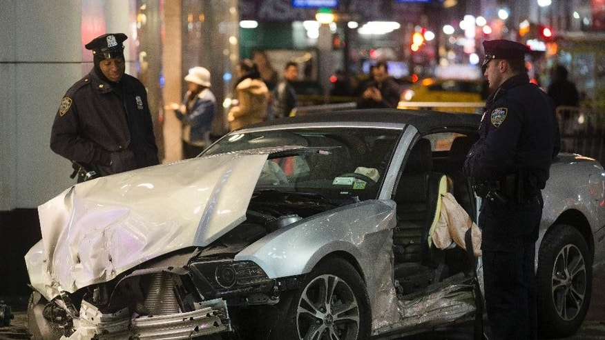 Police stand guard at the scene of a vehicular accident on 34th Street, Thursday, Dec. 11, 2014, in New York. Six people were hurt when the car jumped a curb in midtown Manhattan and struck a group of people around 10 p.m. A fire department spokesman says the injured were taken to Bellevue hospital with serious but non-life threatening injuries. (AP Photo/John Minchillo)