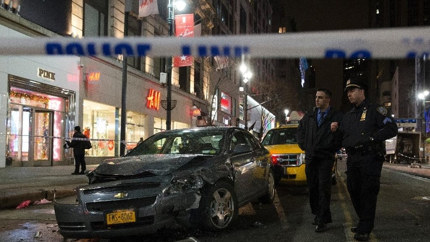 Police survey the scene of a vehicular accident on 34th Street, Thursday, Dec. 11, 2014, in New York. Six people were hurt when the car jumped a curb in midtown Manhattan and struck a group of people around 10 p.m. A fire department spokesman says the injured were taken to Bellevue hospital with serious but non-life threatening injuries. (AP Photo/John Minchillo)