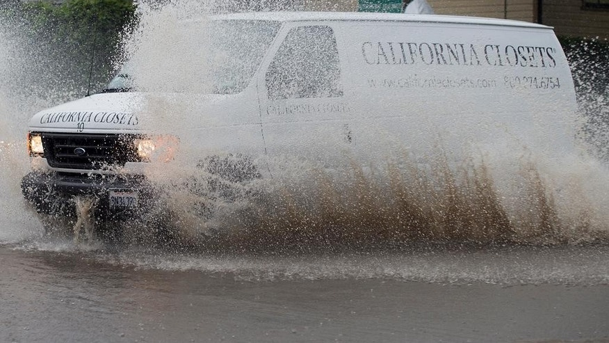 A van navigates a flooded roadway in Berkeley, Calif., on Thursday, Dec. 11, 2014. A powerful storm churned through Northern California Thursday, knocking out power to tens of thousands and delaying commuters while soaking the region with much-needed rain. (AP Photo/Noah Berger)