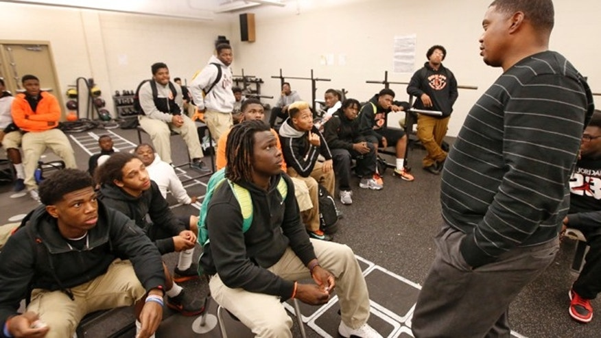 Dec. 1: Douglass High School head football coach Willis Alexander talks with players during a team meeting in Oklahoma City. A judge ruled that the team's loss against Locus Grove will stand despite challenge.