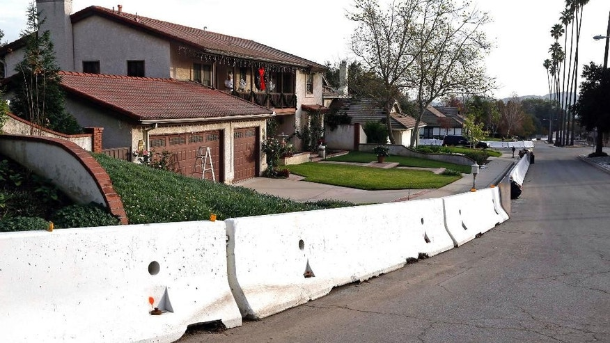 Concrete 'K' rails protect homes from possible flooding in Glendora, Calif., below mountains burned over in widlfires, Wednesday, Dec. 10, 2014. A powerful storm expected to pack hurricane-force winds and heavy rain triggered emergency preparations across Northern California on Wednesday, with residents gathering sand bags, crews clearing storm drains and San Francisco school officials canceling classes for the first time since 9/11. As much as 8 inches of rain could fall on coastal mountains over a 24-hour period starting late Wednesday, the National Weather Service said. Ski resorts in the northern Sierra Nevada could get more than 2 feet of snow. (AP Photo/Nick Ut)