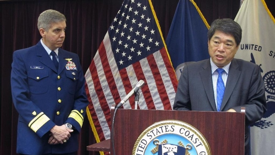 Moon Duk-ho, a representative of the South Korean government, speaks to reporters on Thursday, Dec. 11, 2014, in Juneau, Alaska.  Rear Adm. Dan Abel, left, commander of the U.S. Coast Guard in Alaska listens on. The two men spoke about response efforts following the sinking of a South Korean fishing vessel in the western Bering Sea. (AP Photo/Becky Bohrer)