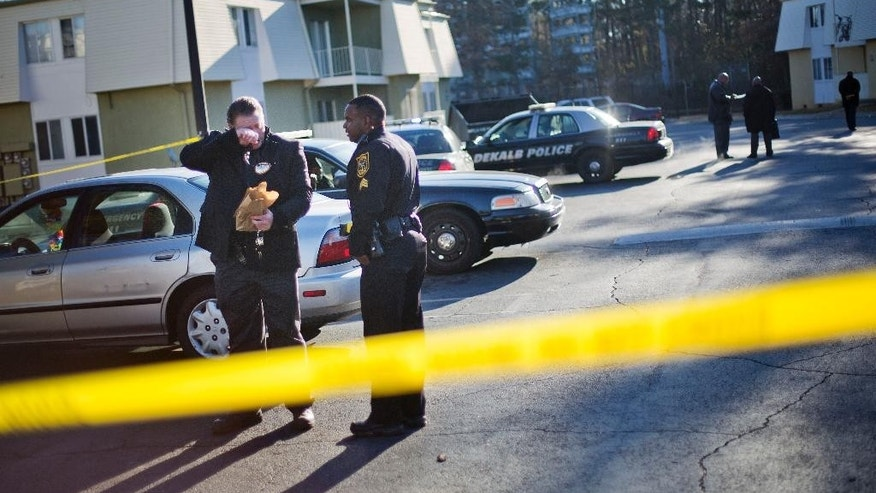 Police investigate the scene of an apartment complex where authorities say two officers were shot leading to a neighborhood search for the suspected gunman, Friday, Dec. 12, 2014, in Decatur, Ga. DeKalb County police Capt. Stephen Fore says both officers suffered what are believed to be non-life threatening injuries. Dozens of police cars swarmed the DeKalb County neighborhood, where several roads were closed after the Friday morning gunfire near Interstate 285. DeKalb County Schools spokesman Quinn Hudson said shortly before 9 a.m. that four nearby schools were on lockdown.(AP Photo/David Goldman)