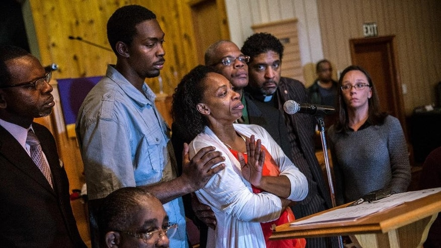 In this Monday, Dec. 1, 2014 photo, Claudia Lacy, center, cries as she thanks the people that showed up at First Baptist Church in Bladenboro, N.C., to listen to the Rev. Dr. William Barber II, president of the North Carolina State Conference of the NAACP, talk about the developments in the investigation of her son's death. Lennon Lacy, a 17-year-old, was found hanging from a swing set in the middle of a trailer park in late August. Surrounding Claudia Lacy are attorney Alan Rogers, left, Wilson Lacy, sitting, Lennon' brother Pierre Lacy, Rev. Gregory D. Taylor, Rev. William Barber II and attorney Heather Rattelade. (AP Photo/The Fayetteville Observer, Raul R. Rubiera) MANDATORY CREDIT