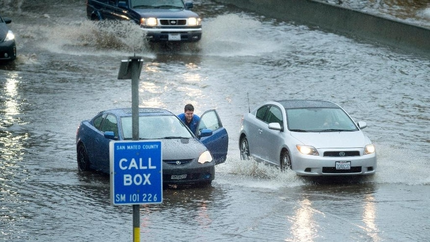 A motorist pushes his car through a flooded stretch of Highway 101 in South San Francisco, Calif., on Thursday, Dec. 11, 2014. A powerful storm churned through Northern California Thursday, knocking out power to tens of thousands and delaying commuters while soaking the region with much-needed rain. (AP Photo/Noah Berger)