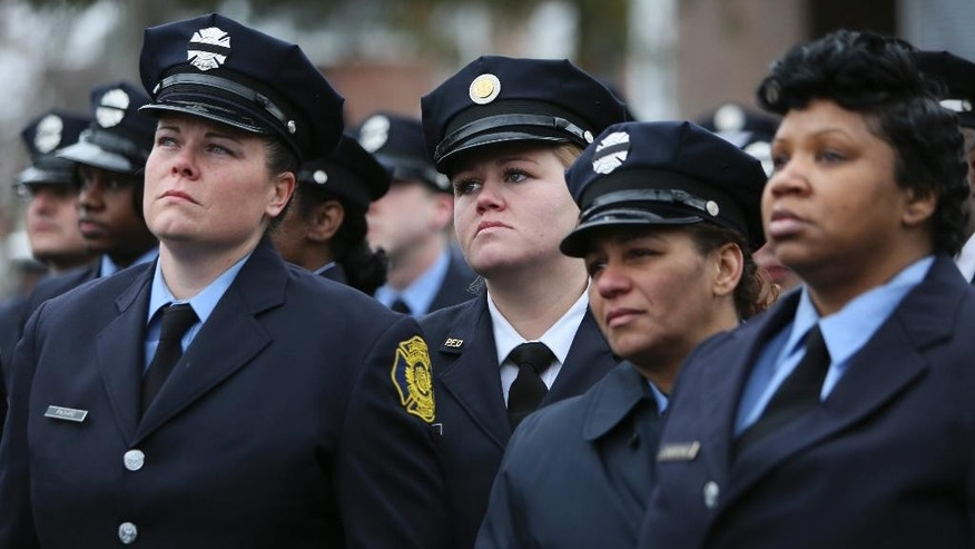 Firefighters Jacquie Packard, left, Brittney Kern-Hughes, third from right, Donna Garrett, second from right and Unique Lawrence, right, listen to remarks from family members during a funeral service in Philadelphia, Saturday Dec. 13, 2014, for fallen Philadelphia firefighter Joyce Craig who died while battling a house fire Tuesday morning.  Craig is the first female Philadelphia firefighter killed in the line of duty. (AP Photo/ Joseph Kaczmarek)