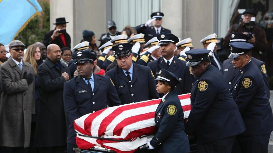 Pallbearers carry the casket of fallen Philadelphia firefighter Joyce Craig, Saturday Dec. 13, 2014, following a funeral service in Philadelphia. Craig, who died while battling a house fire Tuesday morning, is the first female Philadelphia firefighter killed in the line of duty. (AP Photo/ Joseph Kaczmarek)