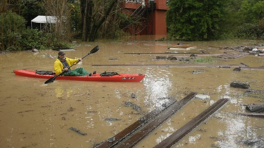 Steve Derst uses a kayak to inspect the damage to the trailer park where he lives Friday, Dec. 12, 2014, in Guerneville, Calif. Derst pulled his home out of the park earlier in the week. While the sun rose Friday in a dry San Francisco sky, the storm's affects lingered in Northern California. In Sonoma County, the Russian River was approaching flood stage and was expected to crest several feet above it by early afternoon. Officials advised residents of about 300 homes to evacuate low-lying areas. (AP Photo/Eric Risberg)