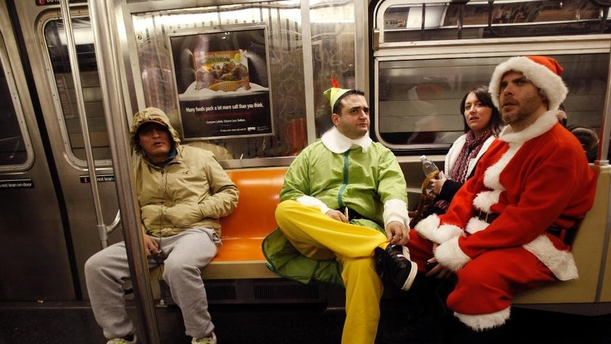 FILE- In this Dec. 11, 2010 file photo, SantaCon participants John Paul, center, dressed as an Elf and Michael Smallwood, dressed as Santa, ride the E train downtown New York. The annual event has faced mounting pressure from politicians, police and community groups as it grew from hundreds to thousands of costumed participants in roughly a decade. This year's festivities fall on the same day as a planned march to protest recent killings of unarmed civilians by police. Santacon organizers are asking celebrants to keep their partying indoors  (AP Photo/Mary Altaffer, File)