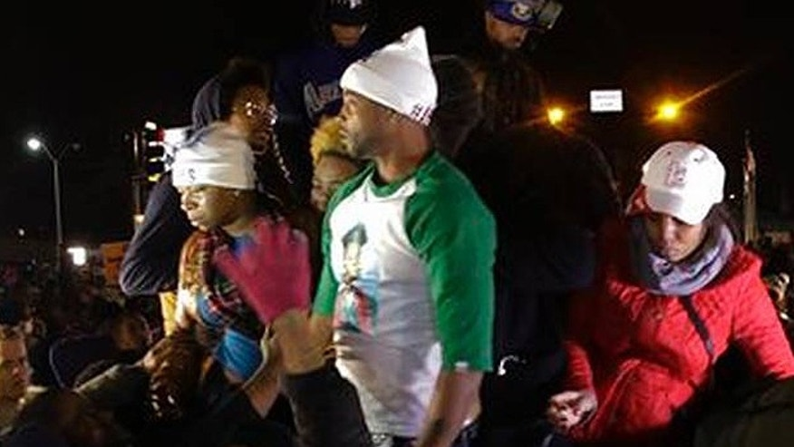 "Louis Head, shown here in the green and white shirt, was videotaped shouting ""Burn this bitch down!"" after a grand jury declined to indict Ferguson Police Officer Darren Wilson in the shooting of Head's stepson, Michael Brown. (AP)"