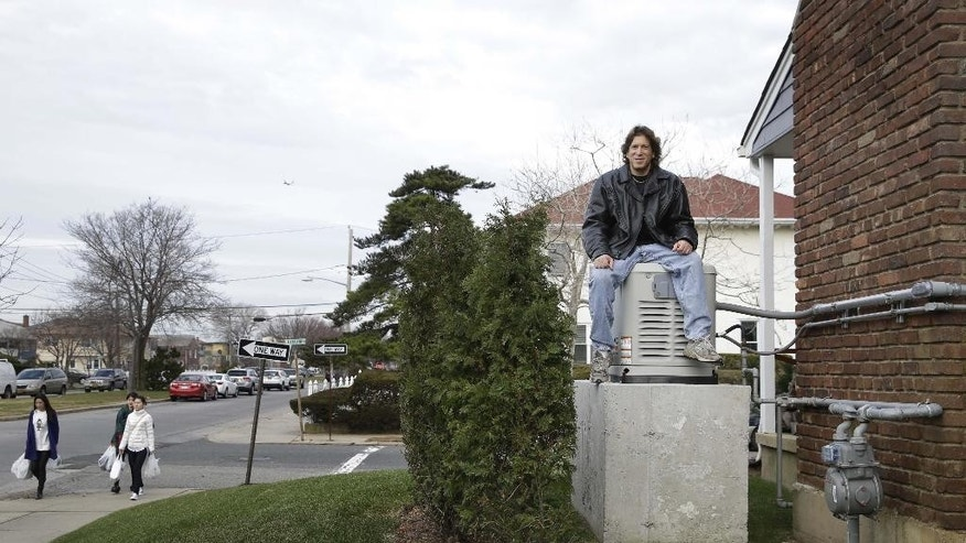 In this Monday, Dec. 1, 2014 photo, Jordan Farkas sits on top of his generator, which is raised eight feet above street level to prevent flooding damage, at his home in Long Beach, N.Y. Some homeowners whose property was ravaged by Superstorm Sandy say they are being denied assistance from other programs because they took out low-interest federal loans right after the storm on the advice of federal workers. (AP Photo/Seth Wenig)