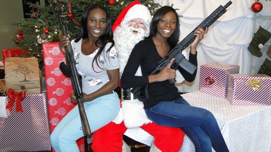 "Dec. 13, 2014: Dasha Washington  and Imani Bowman pose with Santa at the Sandy Springs Gun Club in Georgia. ""We just came in to shoot. We're so excited that Santa is here today,"" said Washington. (Photo Courtesy Sandy Springs Gun Club)"