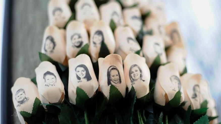 Jan. 14, 2013: In this file photo, white roses with the faces of victims of the Sandy Hook Elementary School shooting are attached to a telephone pole near the school on the one-month anniversary of the shooting that left 26 dead in Newtown, Conn. (AP)