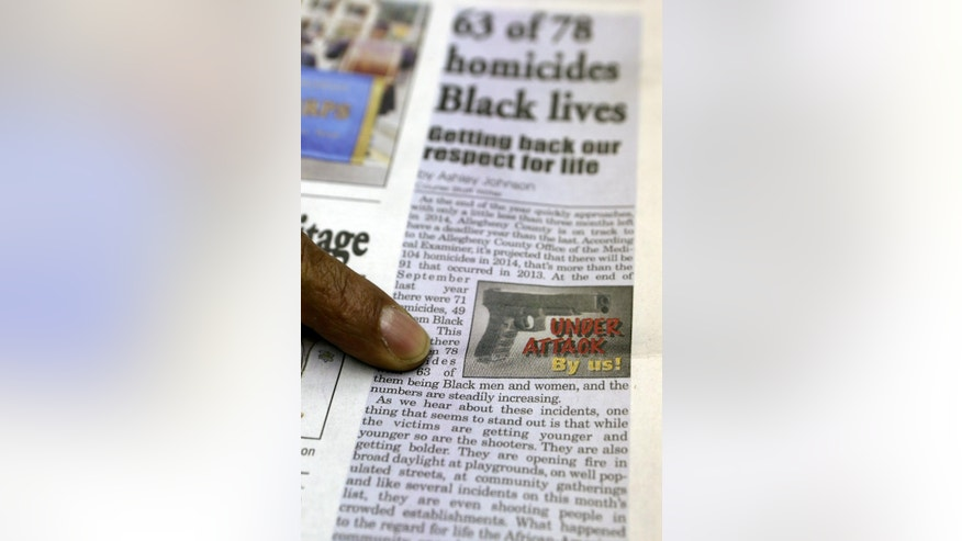 In this Nov. 20, 2014, photo, New Pittsburgh Courier editor and publisher Rod Doss, points out the graphic the paper is using in recent articles focused on black on black violent crime while in the newspaper conference room in Pittsburgh. The Courier, an historic black newspaper, began a campaign with coverage of each homicide almost a decade ago because editors at the Courier simply felt black-on-black killings were not getting the attention they deserved. (AP Photo/Keith Srakocic)