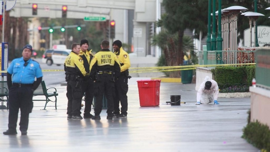 An employee of Logistical Solutions, right, cleans up the scene as Las Vegas police investigate a shooting involving a Regional Transportation Commission security officer and man, pronounced dead at the scene, who was asked to get off of an RTC bus because of a disturbance, outside of the Paris hotel-casino in Las Vegas on Monday, Dec. 15, 2014. The man pulled out a handgun and shot multiple times at the security officer, who responded by firing back and killing the man. (AP Photo/Las Vegas Review-Journal, Chase Stevens)