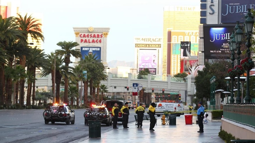 Las Vegas police investigate the scene of a shooting involving a Regional Transportation Commission security officer and man, pronounced dead at the scene, who was asked to get off of an RTC bus because of a disturbance, outside of the Paris hotel-casino in Las Vegas on Monday, Dec. 15, 2014. The man pulled out a handgun and shot multiple times at the security officer, who responded by firing back and killing the man. (AP Photo/Las Vegas Review-Journal, Chase Stevens)