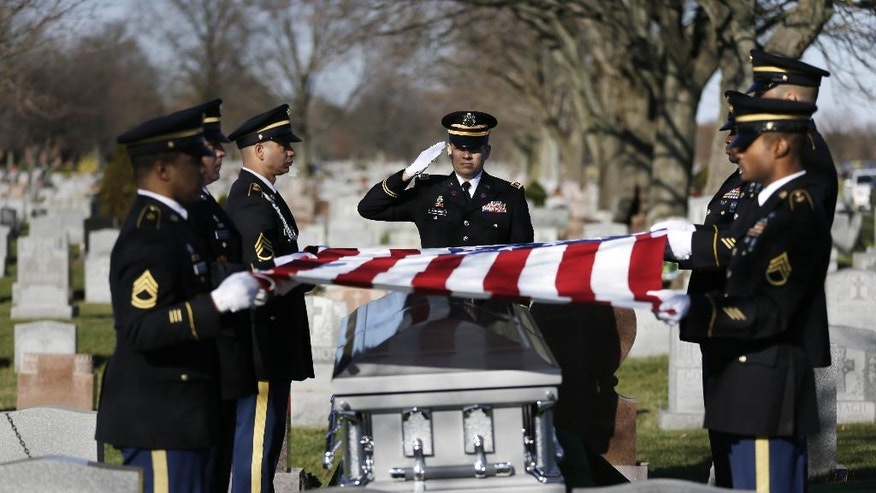 A soldier salutes during a graveside service for Anthony La Rossa in Farmingdale, N.Y., Monday, Dec. 15, 2014. The 18-year-old New York City soldier listed for decades as missing in action during the Korean War is receiving full military honors at a funeral Monday on Long Island. The remains of Pfc. Anthony La Rossa of Brooklyn were returned to the United States by North Korea in the early 1990s, and only recently identified. (AP Photo/Seth Wenig)
